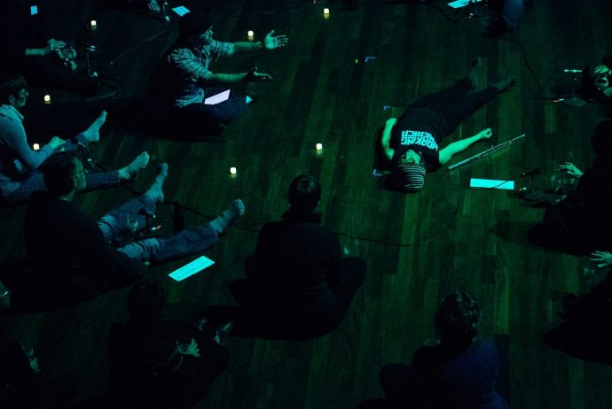 Claire Chase lays on stage during rehearsal, photo by Evan Frost, for Minnesota Public Radio
